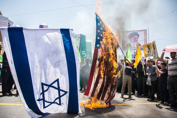 Participants in Tehran's Quds Day rally burn U.S. and Israeli flags, on July 10, 2015. (Image source: ISNA)